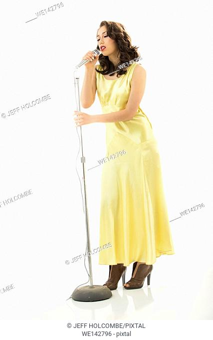 Beautiful young woman full length in vintage yellow dress, singing softly into microphone with eyes nearly closed in an emotional moment