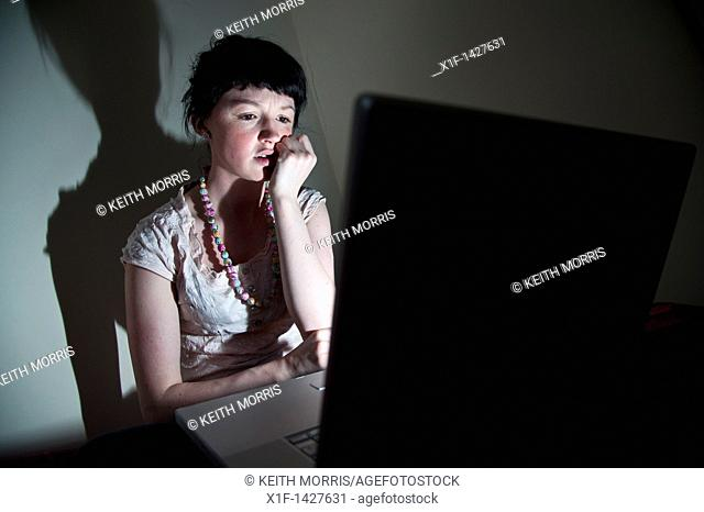 A young woman UK university student working on her laptop computer in her bedroom at home, worried about email virus bug
