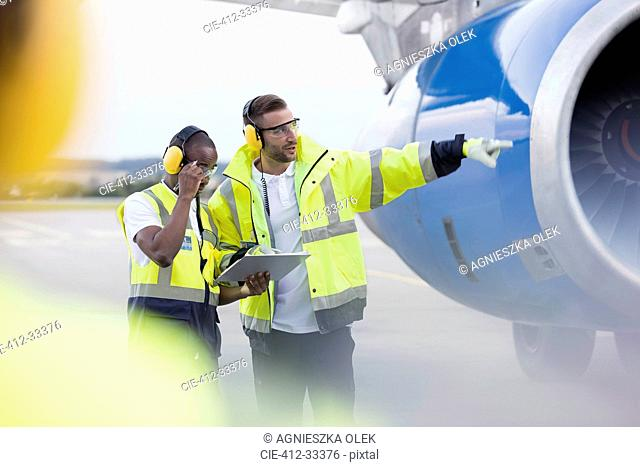 Air traffic controllers with clipboard next to airplane on airport tarmac