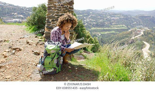 Young female sitting with backpack and map