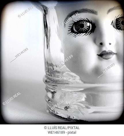 Primer plano de una cabeza de muñeca de porcelana mirando fijamente a la camara desde el interior de un bote de cristal. Close up of a porcelain doll head...