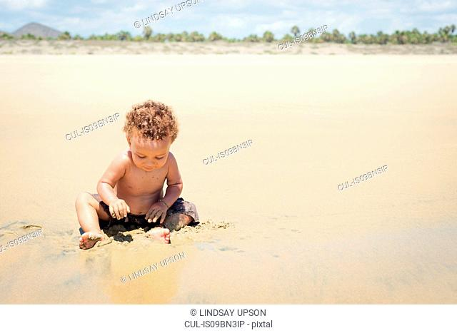 Toddler playing in sand on beach