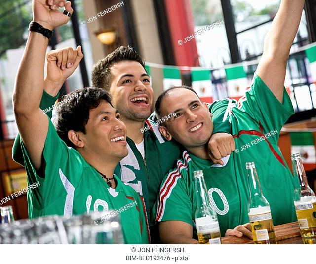 Cheering Hispanic men watching television in sports bar
