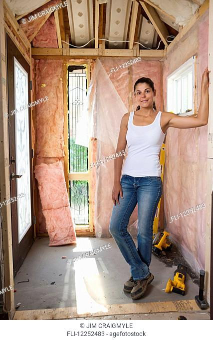 Woman in her 30s at entrance of her home that is being renovated; Bradford, Ontario, Canada