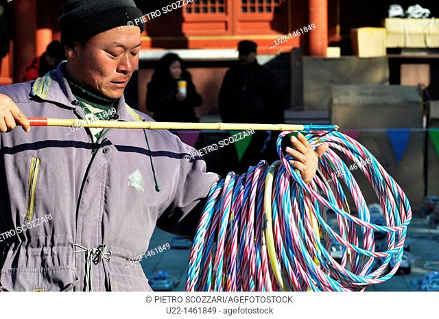 Beijing (China): a man picking up circlets of a game at the Dongyue Temple during the Spring Festival