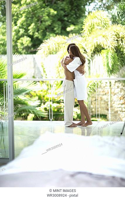 A couple hugging on a balcony
