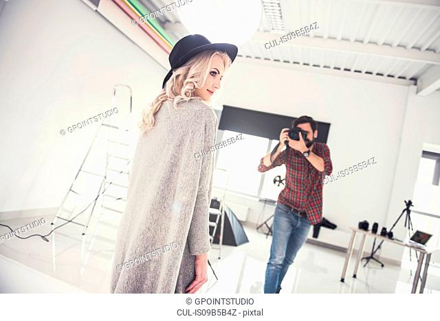 Male photographer photographing female model on studio white background