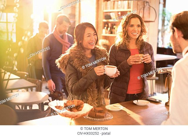 Women talking to barista at cafe counter