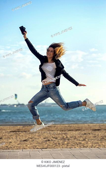 Spain, Puerto Real, woman with camera jumping in the air in front of the sea