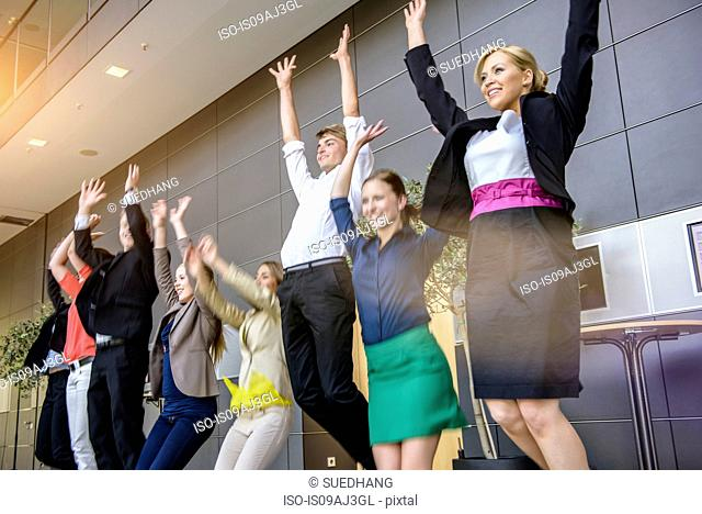 Row of businesswomen and men jumping mid air in office