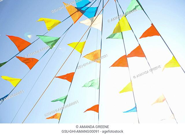 Colorful Pennant Flags Against Blue Sky, Low Angle View