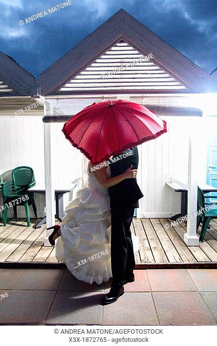 Wedding couple kissing underneath a red umbrella Ostia Rome Italy