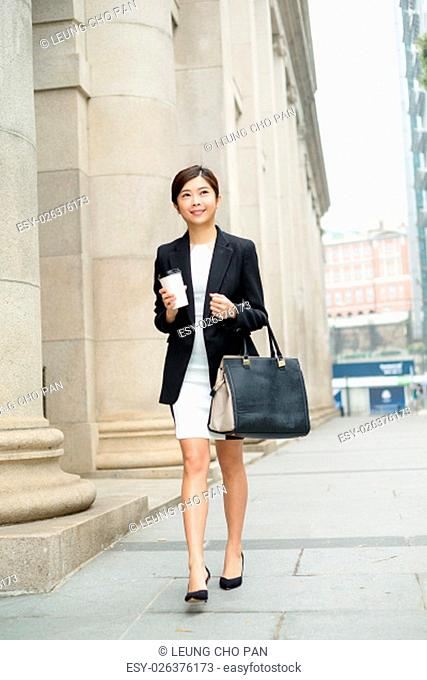 Young businesswoman walking at street
