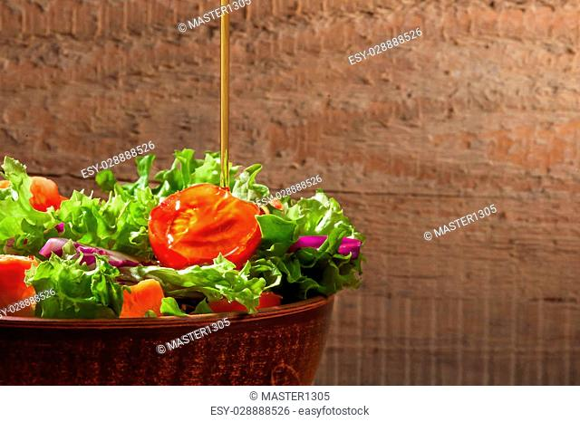 Fresh green organic salade on wooden background. A thin stream of olive oil pouring into salad