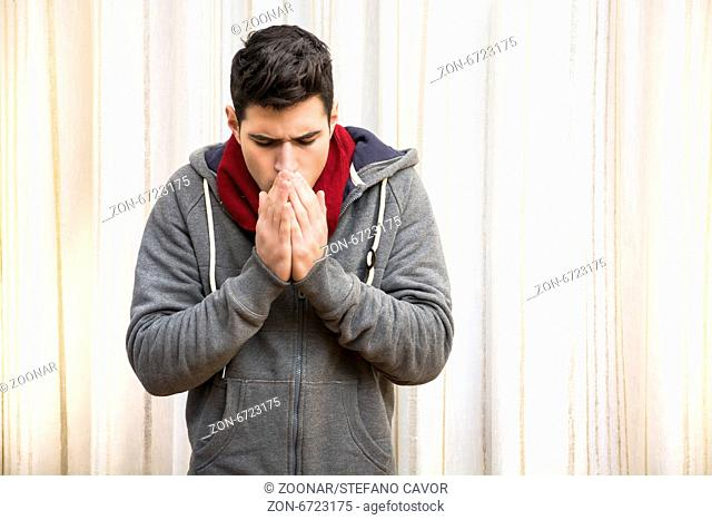 Young man feeling very cold, warming hands with his breath, wearing heavy sweater and scarf