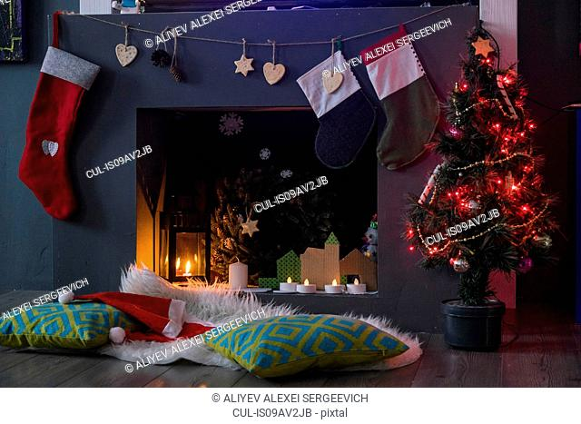Santa hats and cushions in front of christmas tree and fireplace