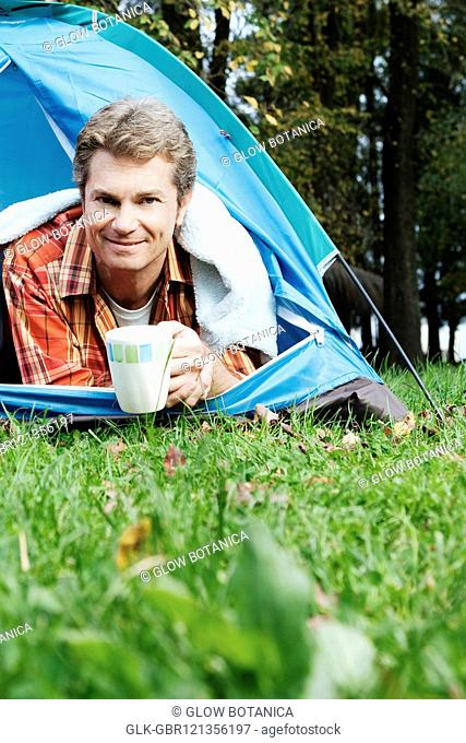 Man lying under a tent drinking tea