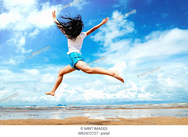 Girl on a sandy beach by the ocean, jumping in the air
