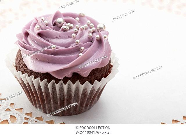 Chocolate cupcake with blackberry icing and silver balls