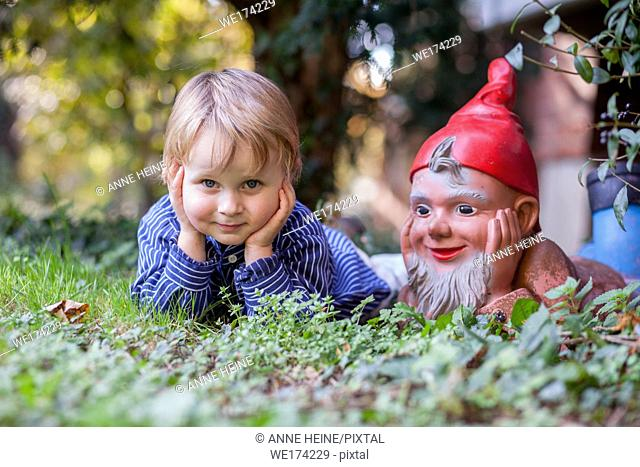 Boy 3 years imitating a garden gnome. Bonn,Germany
