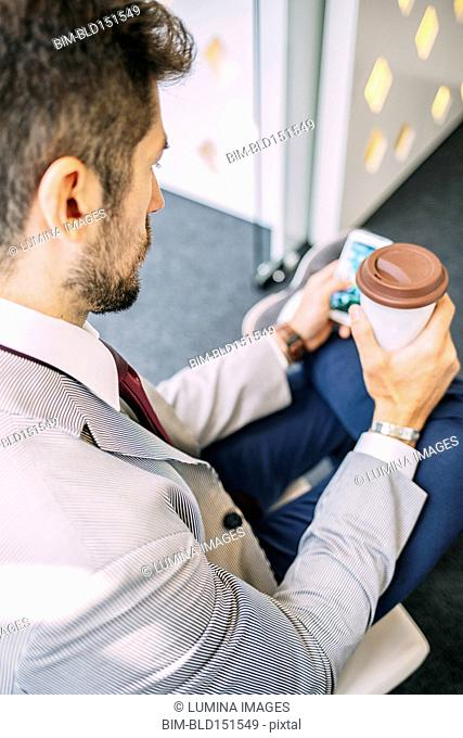 Caucasian businessman drinking coffee and using cell phone
