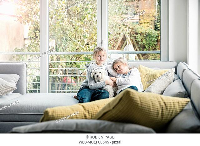 Portrait of two girls with dog on couch in living room
