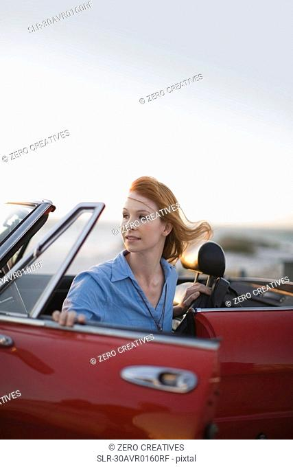 Red haired girl sitting in red car