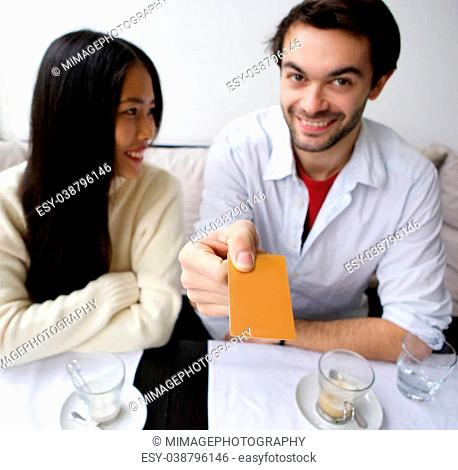 Portrait of a smiling couple paying for meal at restaurant