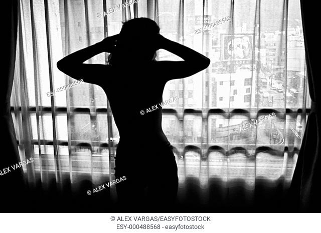 silhouette of japanese woman in sensual position looking through the window of a hotel room  Japan