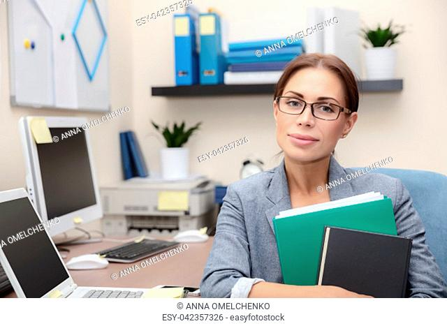Portrait of a serious business woman with documents in hands sitting in the office, make a career in the finance industry, smart people and hard work concept