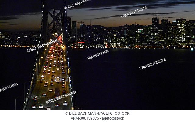 San Francisco California skyline and the Oakland Bay Bridge at evening with traffic on bridge and cars at colorful sky sunset from Treasuire Island