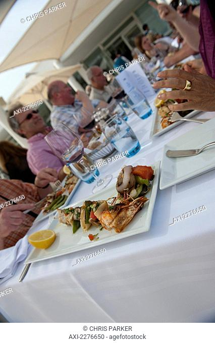 A table of tourists enjoying an alfresco lunch of skewered seafood; Djerba, Tunisia