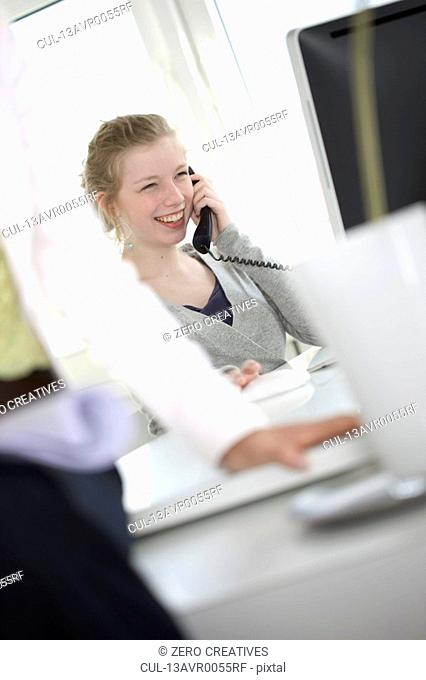 Girl with telephone receiver laughing in