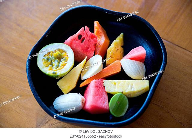 food, eco, bio and summer holidays concept - close up of exotic tropical fruits in bowl