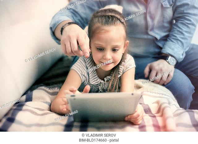 Caucasian father and daughter using digital tablet
