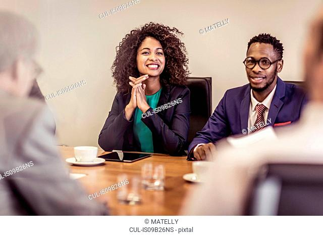Over shoulder view of businessman and woman listening at boardroom meeting