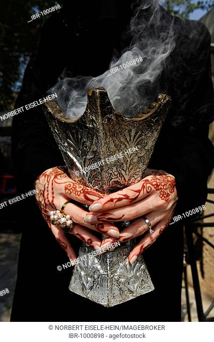 Hands of a woman with henna-painting holding incense holder, Dubai, United Arab Emirates, Middle East