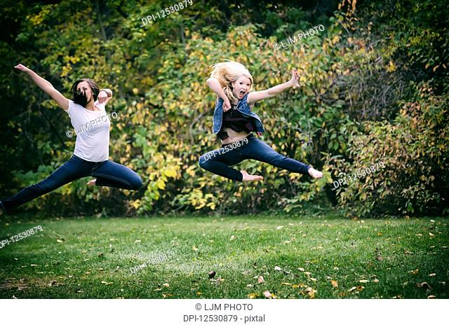 Two Girlfriends Leaping Through The Air Try Doing A Martial Arts Kick Move For Fun Outdoors In A Park On A Fall Evening; Edmonton, Alberta, Canada