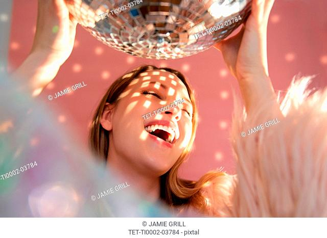 Smiling young woman holding mirror ball