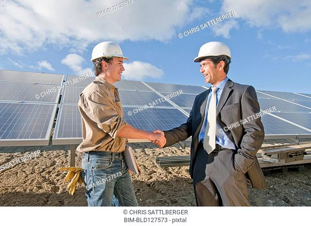 businessman shaking engineer's hand in solar plant