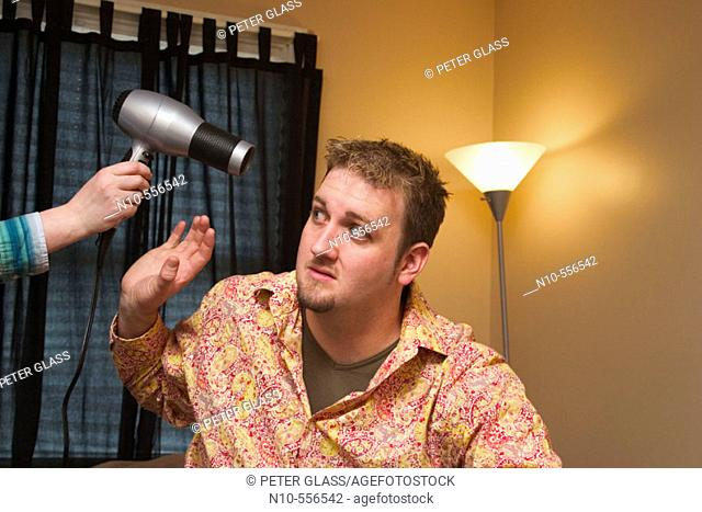 Young man sitting on the bed in his bedroom, with a young woman's hand holding a hair dryer by his head