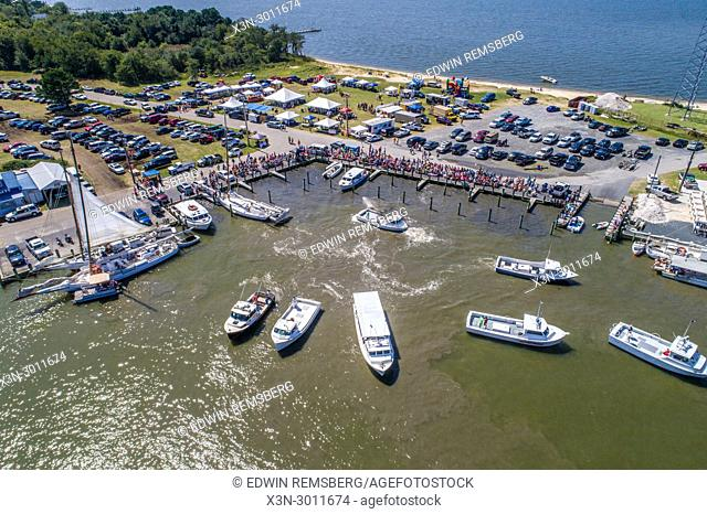 Aerial view festival as crowd gathers along dockside while various boats float anchored near by, Deal Island, Maryland. USA