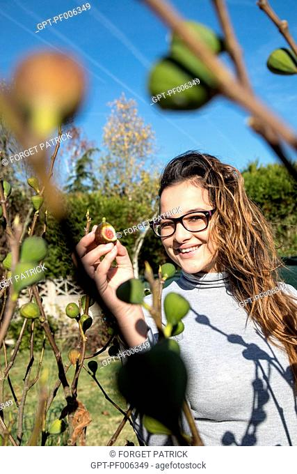 YOUNG WOMAN IN FRONT OF A FIG TREE, EURE-ET-LOIR, FRANCE