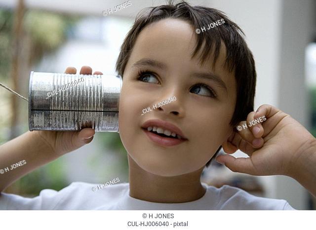 Boy using a tin can as a phone