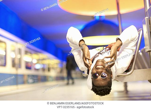 young man laying upside down on bench in underground train station, public transport in Munich, Germany