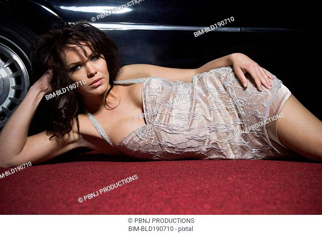Mixed race woman laying on red carpet