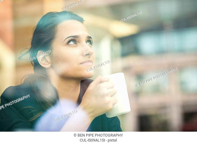 Young businesswoman drinking coffee and looking out of cafe window, London, UK
