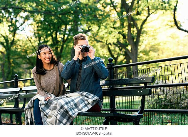 Mid adult man sitting on park bench with girlfriend taking photographs on SLR camera