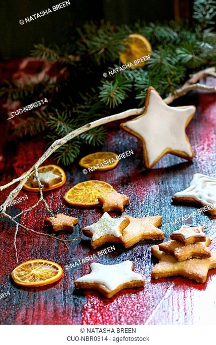 Christmas glazed star shapes cookies with Christmas tree and dry sliced orange over red wooden table. Dark rustic style, day light. View from outside