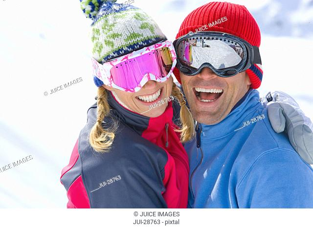 Smiling couple wearing goggles, hugging
